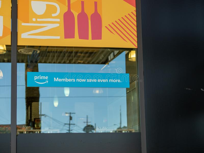 Amazon Prime members now save even more sign outside of Whole Foods location stock photo