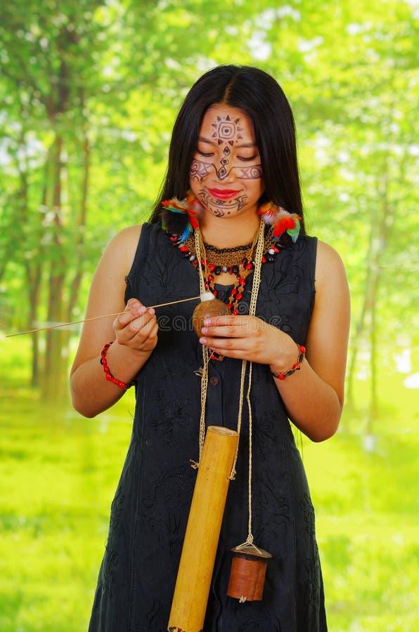 Amazonian exotisk kvinna, ansikts- målarfärg, svart klänning, fall för pilar och liten träflaska som hänger runt om hals som appl fotografering för bildbyråer