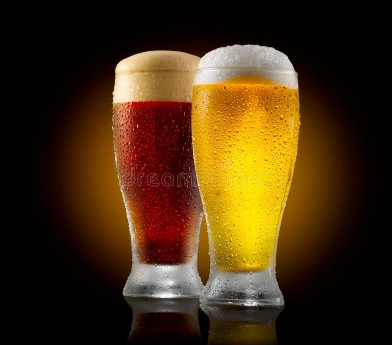 Ambachtbier Twee glazen koud licht en donker die bier op zwarte wordt geïsoleerd stock afbeeldingen