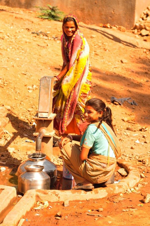 Ambaji: Dos mujeres indias jovenes que llenan sus agua-cuencos imagen de archivo libre de regalías