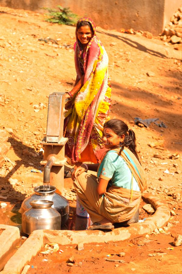 Ambaji: Two young indian women filling their water-bowls royalty free stock image