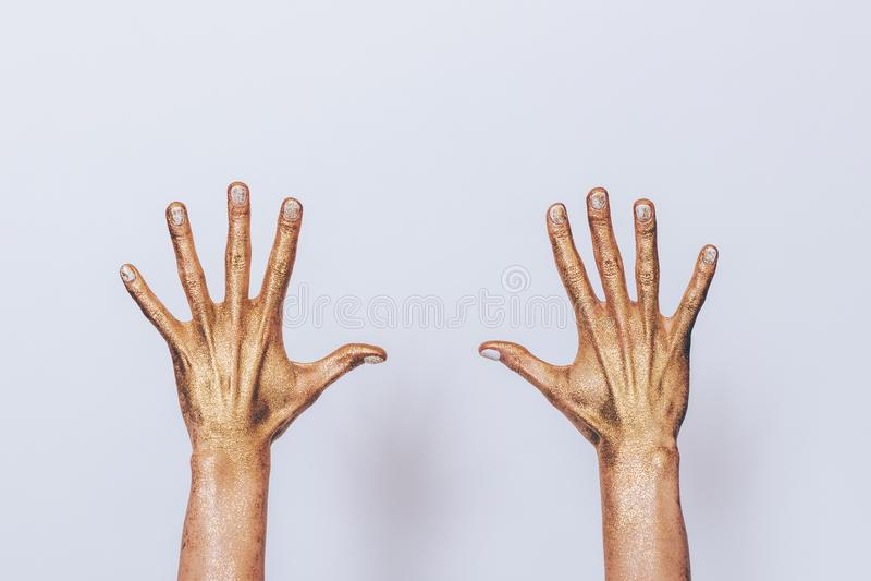 Ambas as mãos da mulher pintaram mostrar dourado das lantejoulas fotografia de stock