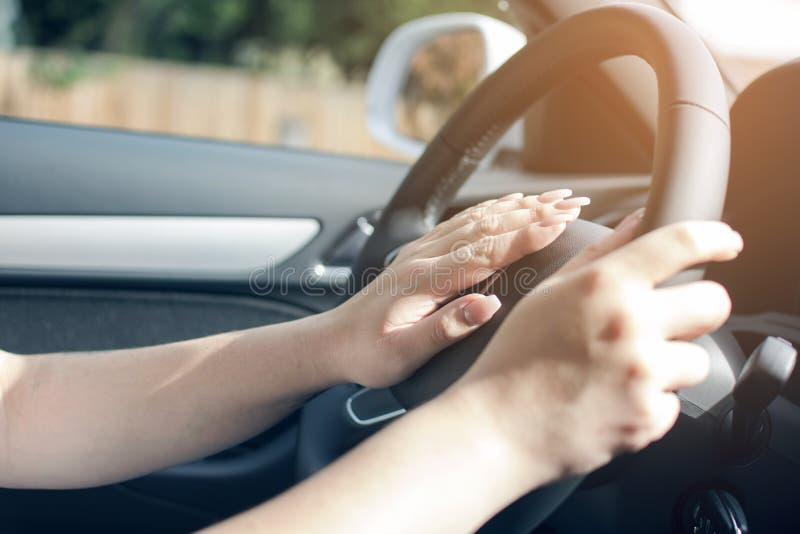 Ambas manos de la rueda conmovedora de la mujer que conduce la mano izquierda conducen el coche, imagen de archivo libre de regalías