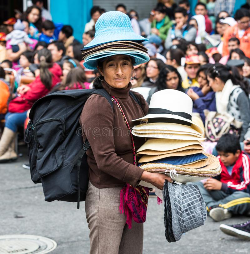 Ambato, Ecuador / Feb 15, 2015 - Hat vendor sells her wares. To people waiting for the Canaval parade to start royalty free stock photography