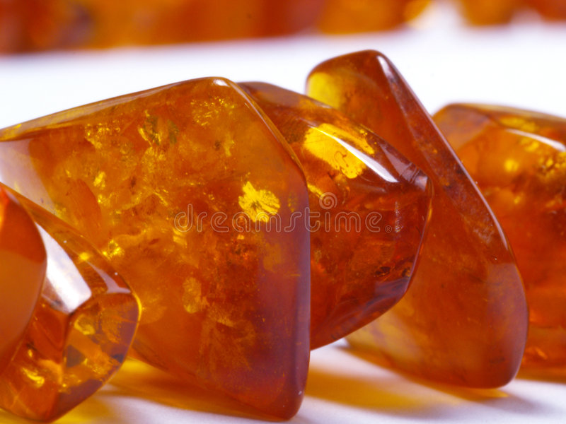Amber bead. Detail amber bead on off- white background close up stock photo