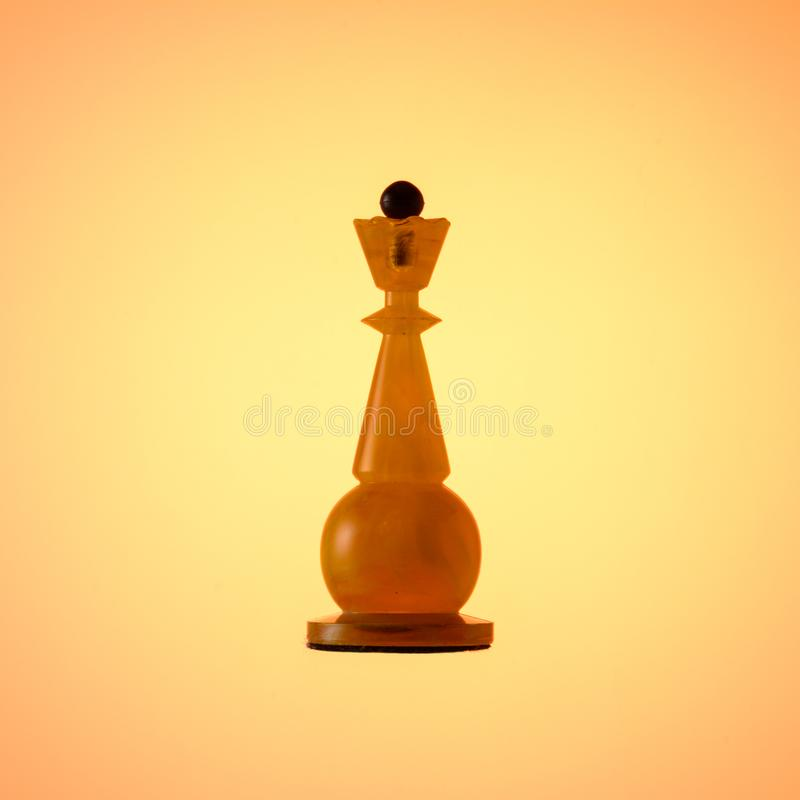 Amber chess set. Chess piece White Queen on gold gradient background. stock image