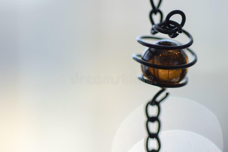 Amber coloreed glasparel in sprial metaal plaatsend met neutrale achtergrond royalty-vrije stock afbeeldingen