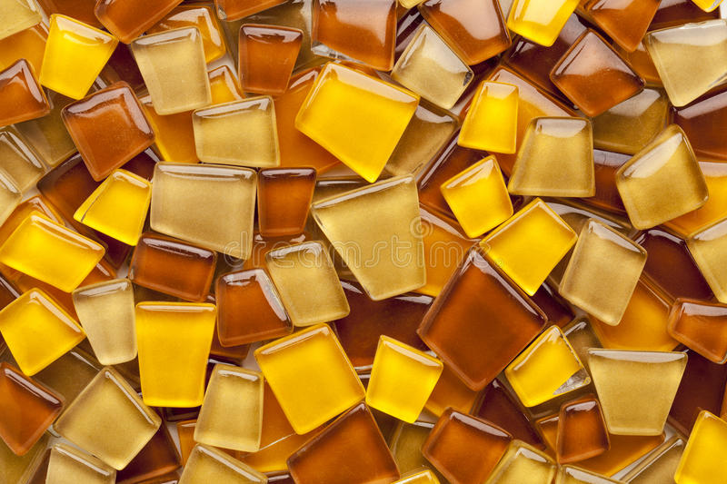 Amber glass mosaic tiles. Random background of yellow, brown and amber glass mosaic tiles stock photography