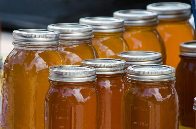Amber jars of honey stock photography