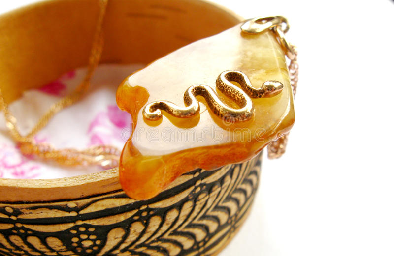 Amber necklace with a gold snake on it. This is an amber necklace with a gold snake on it stock photo