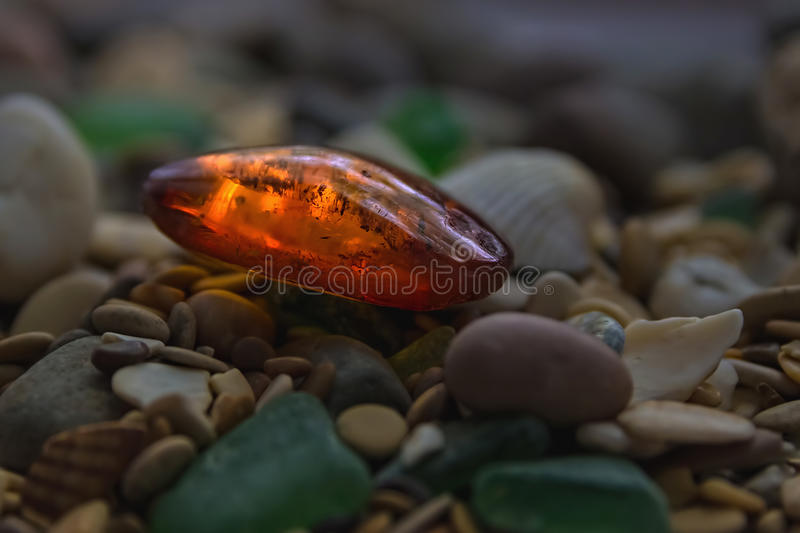 Amber stone. Mineral amber. Rosin yellow amber. Sunstone on a beach of pebbles. Amber stone. Mineral amber. Rosin yellow amber. Sunstone on a beach of pebbles royalty free stock photography