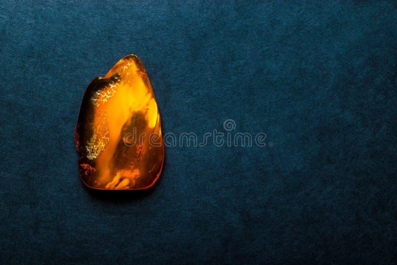 Amber Stone op Donkerblauwe Oppervlakte Als achtergrond met Vrije Ruimte stock foto