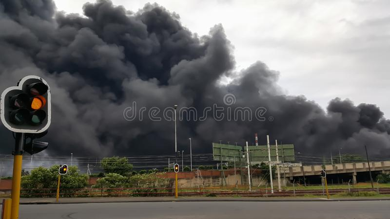 Traffic light in city with black toxic smoke in the background. stock photos
