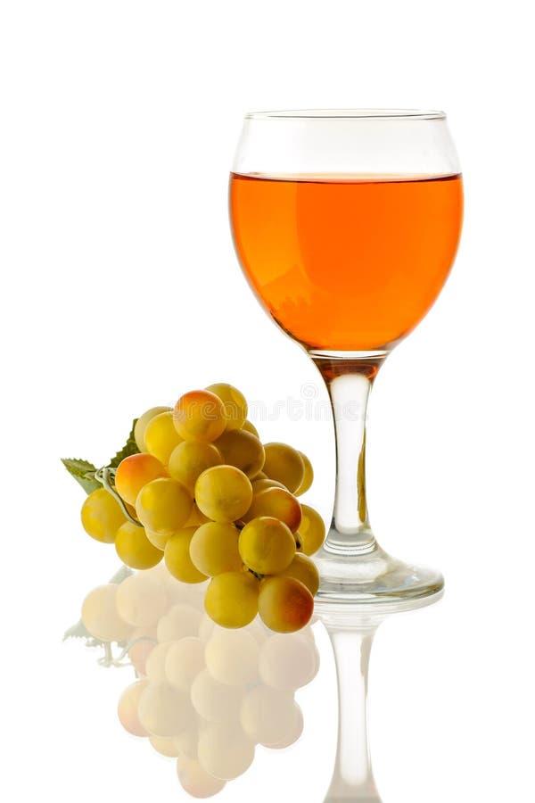 Amber Wine Wein in einem Glas und eine Handvoll weiße Trauben lizenzfreies stockfoto