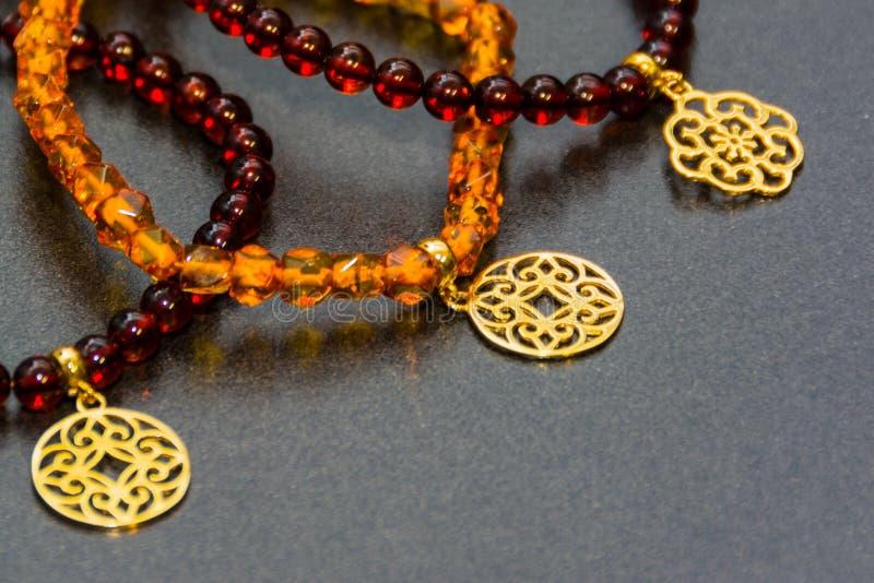 Amberarmbanden met gouden tegenhangers royalty-vrije stock foto's