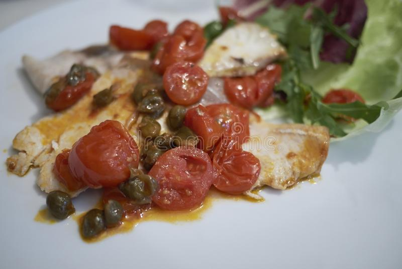 Amberjack vissen met tomaten en kappertjes stock foto