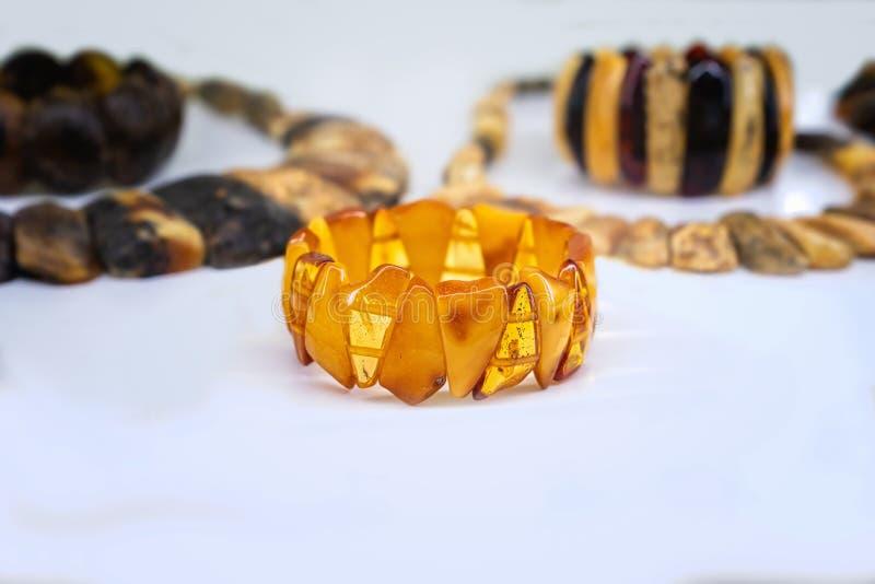 Amberkleurige nekletjes en armbanden op een witte achtergrond stock foto's