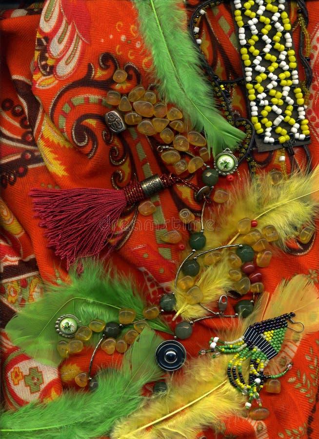 Amberparels die op kleurrijke sjaal met knopen en veren liggen stock foto