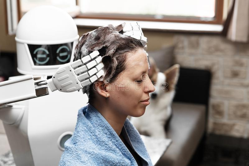 Ambient assisted living household robot is washing the hair of an adult woman. Concepts like hairdresser cyborg or artificial intelligence robotic royalty free stock images