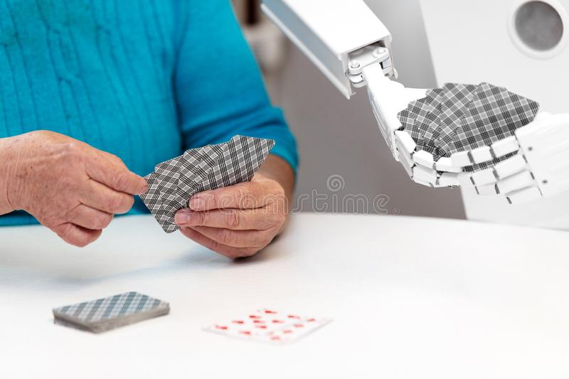 Ambient assisted living service robot is playing a card game with a senior adult woman. Ambient assisted living service robot is pla card game with a senior royalty free stock photos