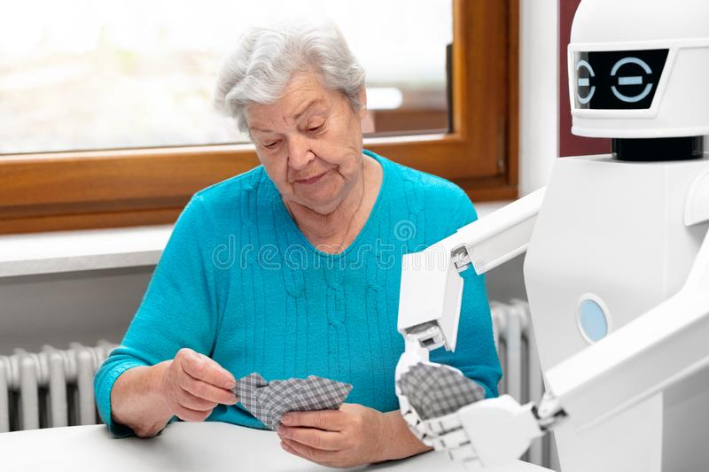 Ambient assisted living service robot is playing a card game with a senior adult woman. Concepts like robotic caregiver in the household or old folks home stock photography