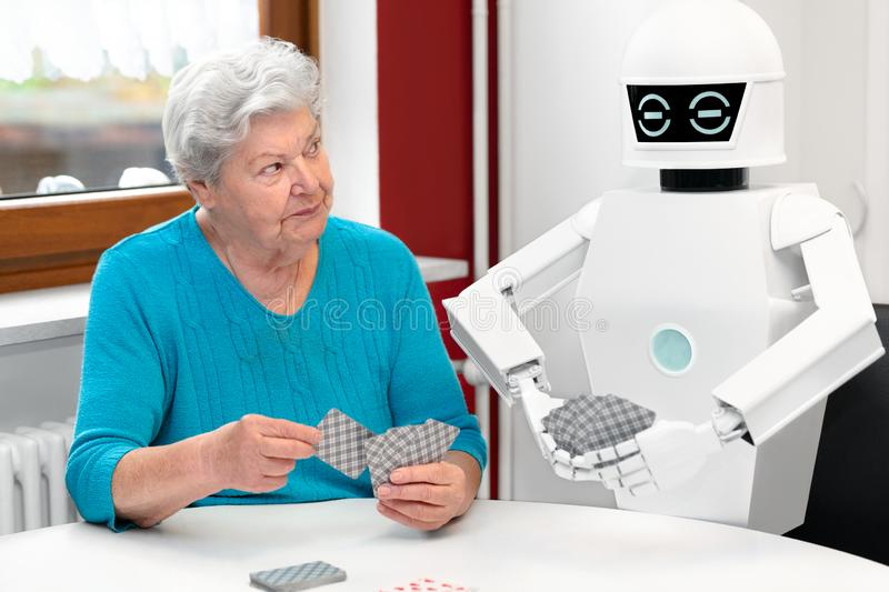 Ambient assisted living service robot is playing a card game with a senior adult woman. Concepts like robotic caregiver in the household or old folks home stock photos