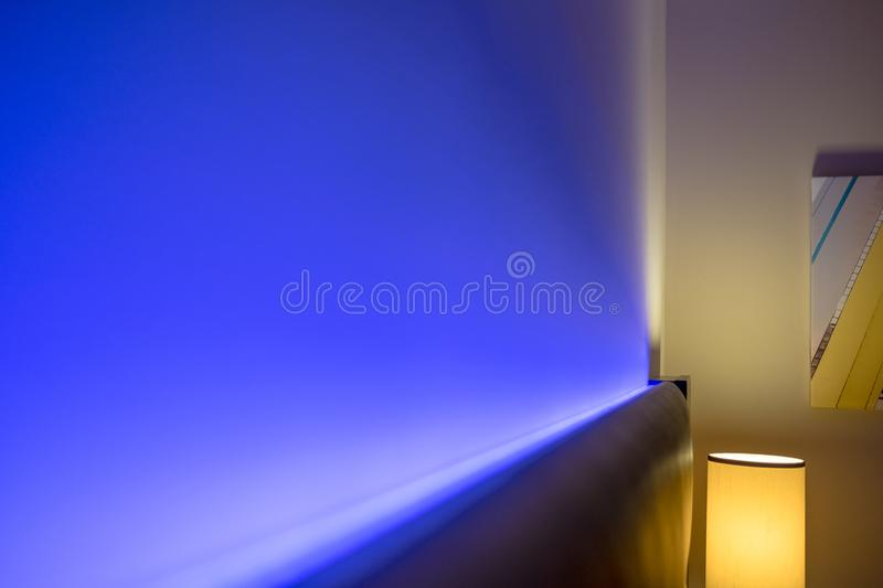 Ambient blue lighting seen illuminated behind a headboard in a luxury apartment. The blue colour creates a relaxing atmosphere for the evening. Also in view is royalty free stock photo