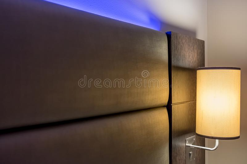 Ambient blue lighting seen illuminated behind a headboard in a luxury apartment. The blue colour creates a relaxing atmosphere for the evening. Also in view is stock photos