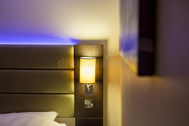 Ambient blue lighting seen illuminated behind a headboard in a luxury apartment. The blue colour creates a relaxing atmosphere for the evening. Also in view is stock photography