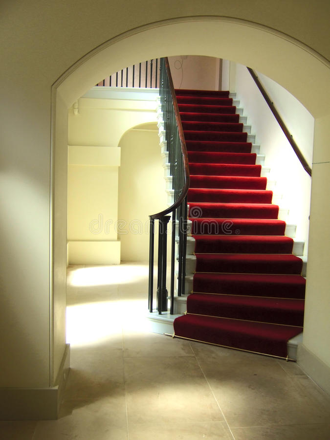 Ambient stairwell. A stairwell with a red carpet, and ambient day lighting royalty free stock image