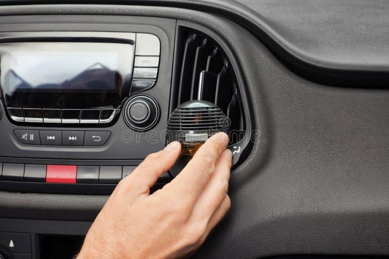 Ambientador de aire de regulación del hombre cerca de la ventilación en coche foto de archivo libre de regalías