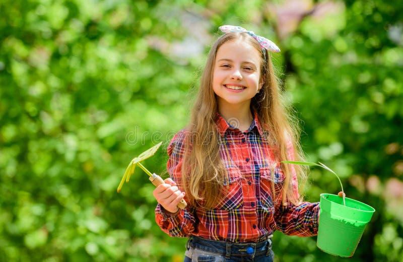 ambiente da ecologia O dia das crian?as felizes menina com ferramentas de jardinagem Dia de terra pa?s da vila da mola ver?o imagens de stock royalty free