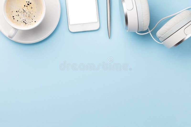 Ambiente di lavoro blu con smartphone e caffè immagine stock libera da diritti