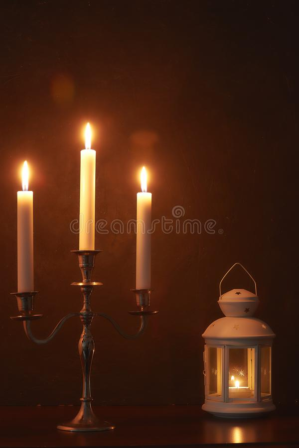 Ambiente familiar quieto na noite pela luz de vela As velas brancas queimam-se na obscuridade composição calma foto de stock