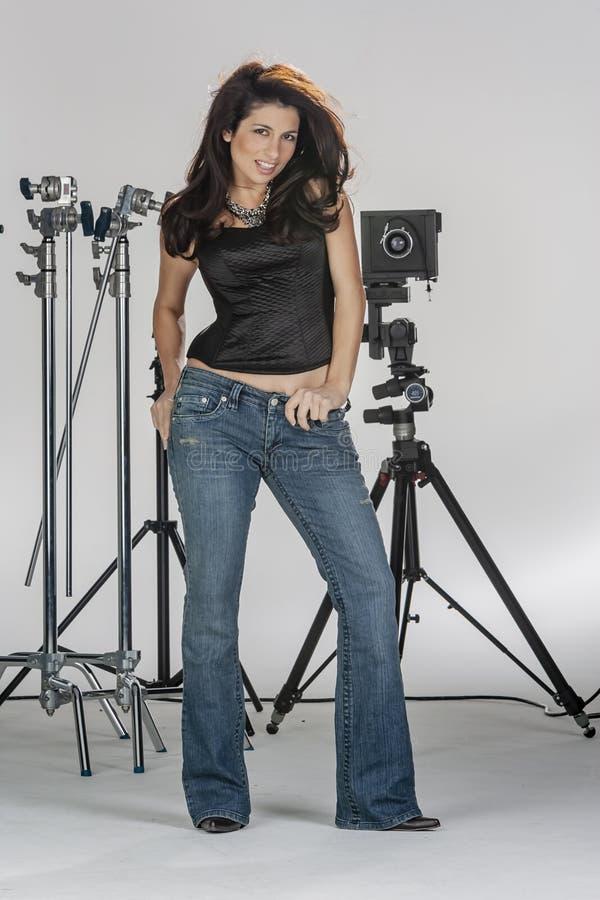 Ambiente moreno lindo do estúdio de Poses In A do modelo contra um equipamento branco da câmera da terra arrendada do fundo imagens de stock