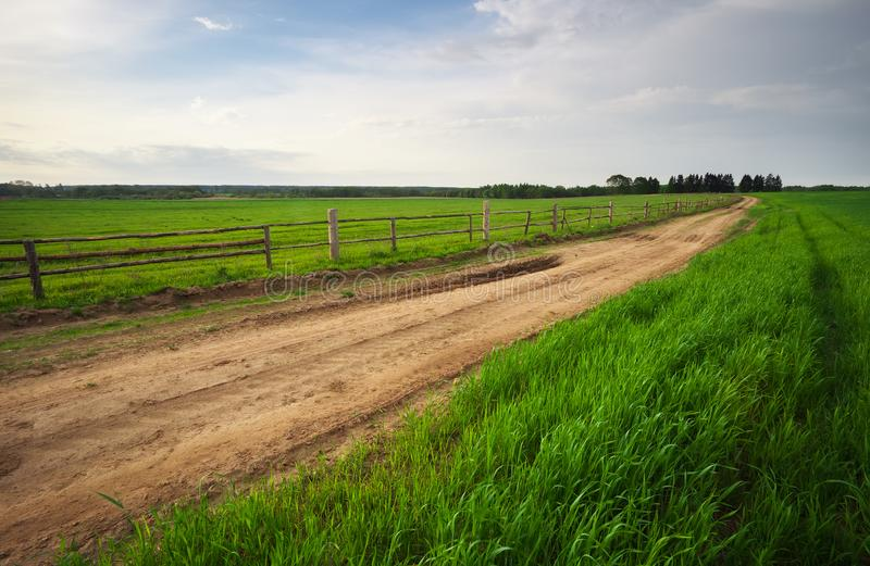 Ambiente rural con la cerca de madera al lado del camino fotos de archivo