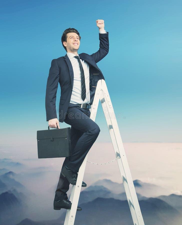 Ambitiös affärsman som försöker att få till överkanten arkivfoto