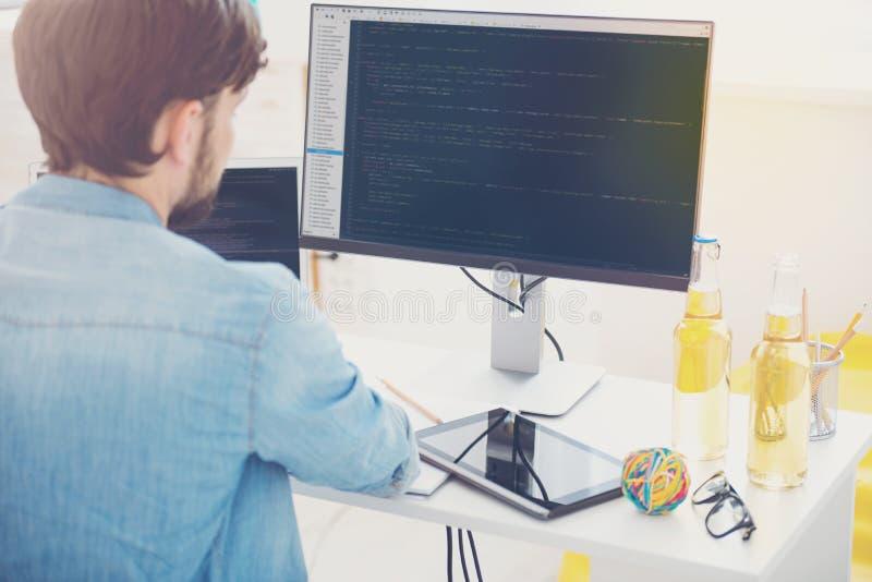 Ambitiös programmerare som arbetar på en dator i ett kontor arkivbild