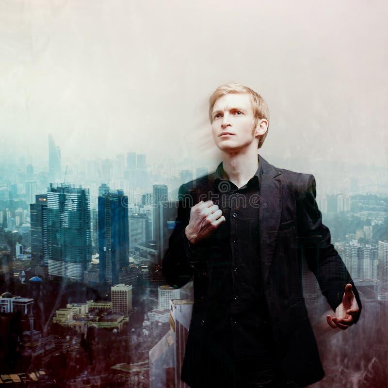 Ambitiös ung man på bakgrund av megalopolisen, dubbel exponering fotografering för bildbyråer