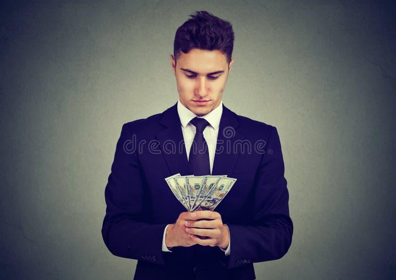 Ambitieuze jonge bedrijfsmens met geld stock foto's