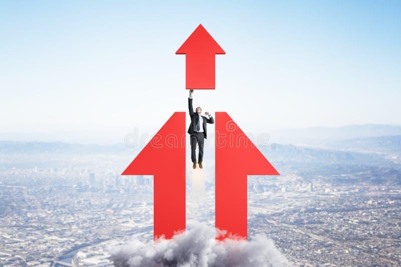 Ambition et concept de but avec un homme d'affaires décoller en direction de la flèche rouge image libre de droits