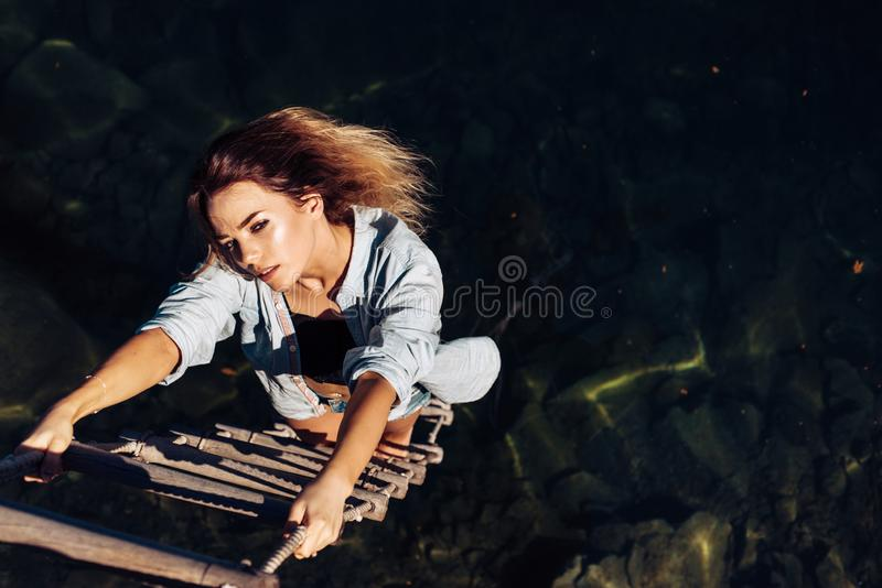 Ambition wings her spirit. woman climbing up rope ladder. Sensual woman hang on rope over water surface. Pretty royalty free stock photos