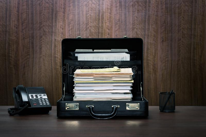 Overtime! Tall stack of files and folders in black leather briefcase on desk with phone stock photo