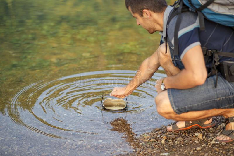 Ambitious traveler is collecting water to the bucket from the lake stock photo