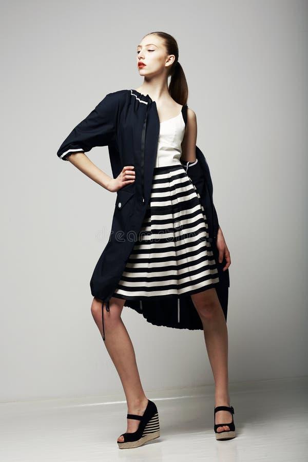 Ambizioni. Brunette onorato sicuro in mackintosh impermeabile nero. Stile di Vogue fotografie stock libere da diritti