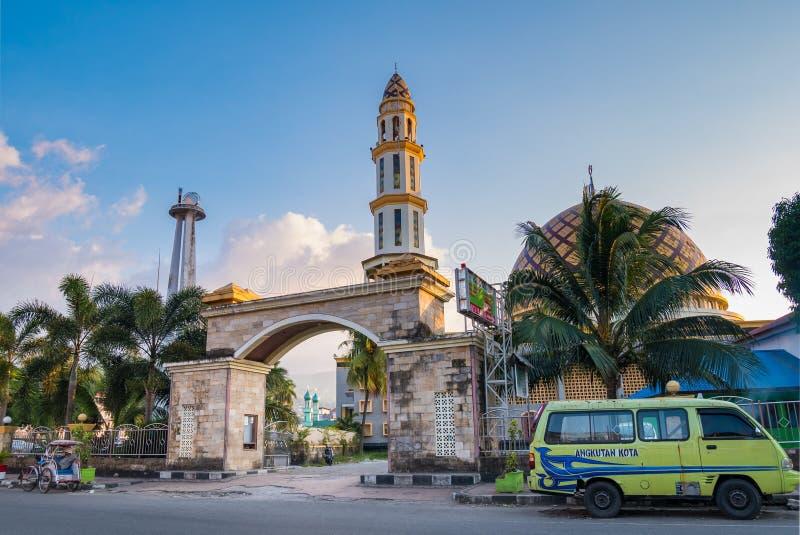 Ambon, Indonésia - 7 de outubro de 2018: mesquita da rua e mini camionete verde angkot na cidade de Ambon, Molucanos, Indonésia imagem de stock royalty free