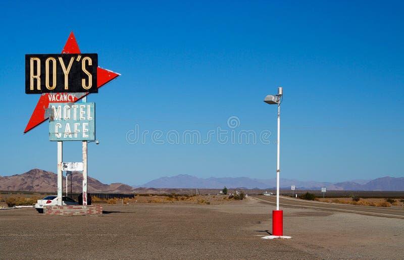 AMBOY KALIFORNIEN, USA - AUGUSTI 8 2009: Isolerat tecken av Roys motell och kafé mot blå himmel på Route 66 med bergskedja royaltyfria foton
