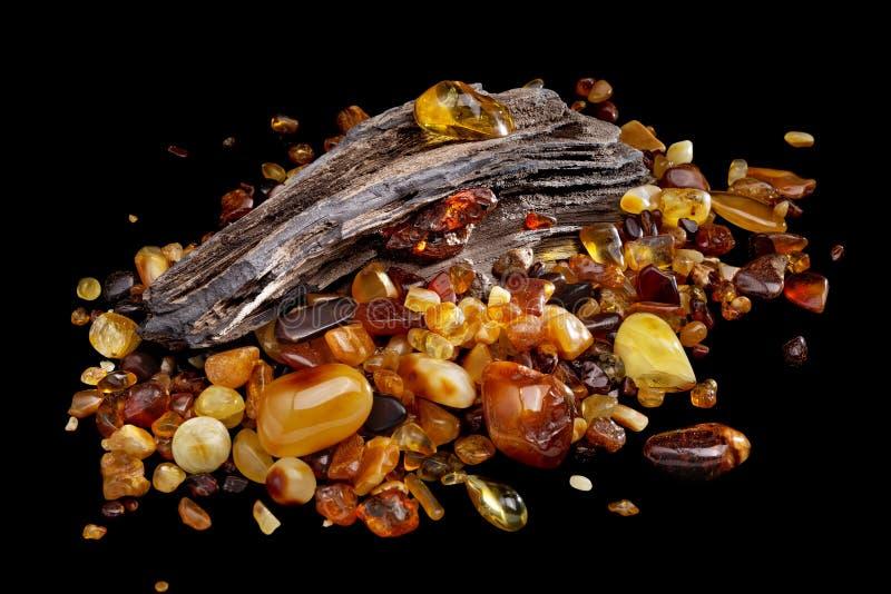 Ambra naturale Molti pezzi di colori differenti di ambra naturale sul grande pezzo di legno lapidato fotografie stock