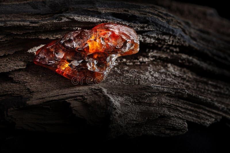 Ambra naturale Un pezzo di ambra naturale trasparente dei semi gialli e rossi sul pezzo di legno lapidato fotografia stock libera da diritti
