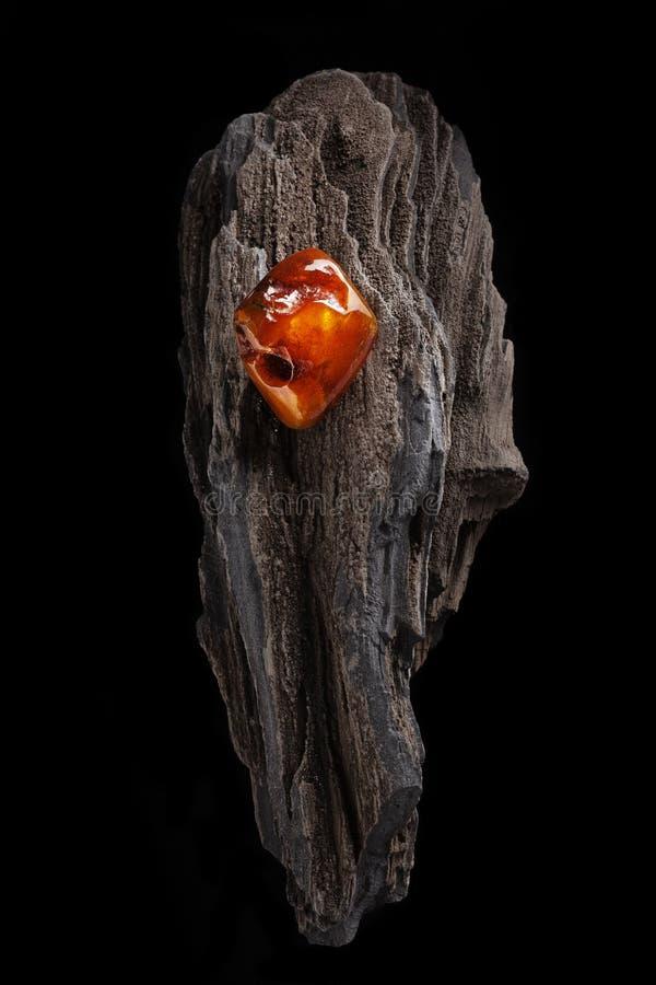 Ambra naturale Un pezzo di ambra naturale trasparente dei semi gialli e rossi sul pezzo di legno lapidato fotografia stock